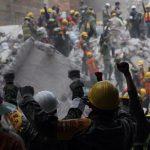 Rescatistas alzan las manos para que todos guarden silencio y puedan escucharlas víctimas debajo de los escombros./ Foto: Sashenka Gutiérrez, EPA